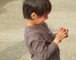 Un bambino gioca con delle viti rinvenute a terra.